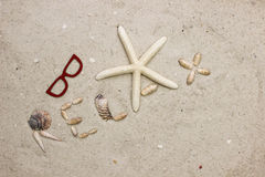 La palabra SE RELAJA en la playa arenosa con las gafas de sol Foto de archivo