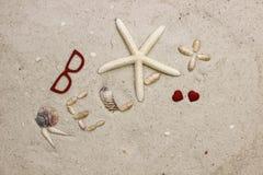 La palabra SE RELAJA en la playa arenosa con los corazones rojos Fotos de archivo libres de regalías