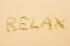 La palabra se relaja escrito en la arena Foto de archivo libre de regalías