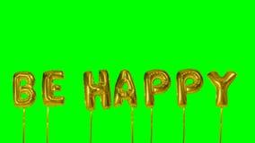 La palabra sea feliz de las letras de oro del globo del helio que flotan en la pantalla verde - almacen de video