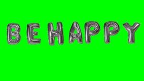 La palabra sea feliz de las letras de plata del globo del helio que flotan en la pantalla verde - almacen de video