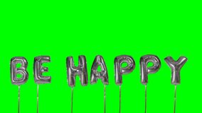 La palabra sea feliz de las letras de plata del globo del helio que flotan en la pantalla verde - metrajes