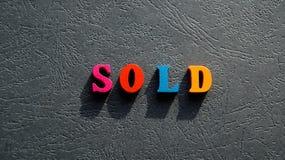 La palabra SOLD hizo de letras de madera coloreadas en la tabla el color oscuro Foto de archivo libre de regalías