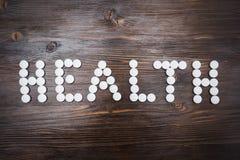 La palabra y el x22; health& x22; se presenta con las píldoras blancas grandes en un fondo de madera oscuro Imagen de archivo libre de regalías