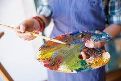 La paleta con las pinturas mezcladas holded por las manos del artista de la mujer foto de archivo