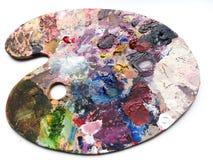 La paleta de los artistas con colores se mezcla sobre el fondo blanco Foto de archivo