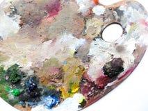 La paleta de los artistas con colores se mezcla sobre el fondo blanco Fotos de archivo libres de regalías