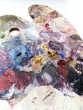 La paleta de los artistas con colores se mezcla sobre el fondo blanco Fotografía de archivo