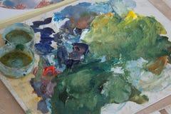 La paleta del artista, pintura de aceite mezclada en el tablero Lío creativo en la tabla preparación para el proceso de dibujo foto de archivo