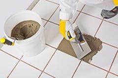 La paleta del trabajador repara el ti de los azulejos Imagenes de archivo