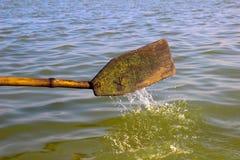 La palette en bois d'aviron a plongé dans l'eau dans un bateau à rames propulsant en avant images libres de droits
