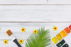 La palette et le pinceau d'aquarelle décorent des feuilles de fougère et des fleurs de papier jaunes image stock