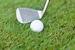La palla da golf ed il ferro su erba verde dettagliano la macro Fotografia Stock