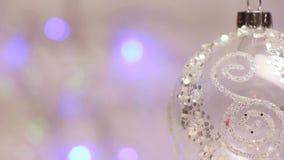 La palla decorativa del ` s del nuovo anno gira contro lo sfondo delle lanterne luccicanti blu, aereo della midle-scala stock footage