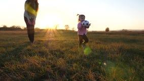 La palla dei giochi da bambini sul campo, madre si occupa della figlia il bambino getta le mani di pallone da calcio su erba nel  stock footage