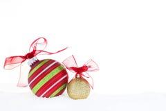 La palla dell'oro di Red Green di Natale orna la neve rossa del nastro Fotografie Stock