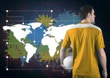 La palla della tenuta del giocatore di football americano accanto alla mappa variopinta con pittura schizza sul fondo della paret Immagine Stock Libera da Diritti