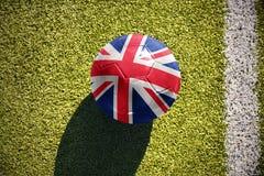 La palla di calcio con la bandiera nazionale della Gran Bretagna si trova sul campo Fotografie Stock