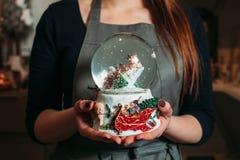 La palla di neve di vetro di natale in femmina passa il primo piano Fotografie Stock