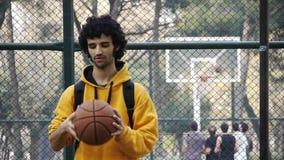 La palla di pallacanestro del gioco del giovane accende il gioco di sport dello streetball del dito stock footage
