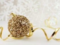 La palla dorata di natale con il nastro sopra ammorbidisce il fondo leggero dei fiocchi di neve nei toni caldi Immagine Stock