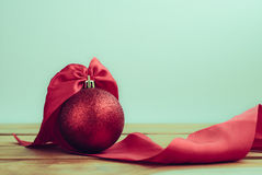 la palla rossa di Natale con il nastro sulla tavola di legno e la copia spaziano indietro Fotografia Stock