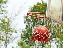 La pallacanestro cade attraverso il cerchio e la rete di pallacanestro Immagine Stock Libera da Diritti