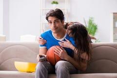 La pallacanestro di sorveglianza dell'uomo con la sua moglie immagine stock