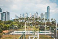 La pallacanestro ed il calcio sollecitano all'aperto con il fondo dell'orizzonte della città Fotografia Stock Libera da Diritti