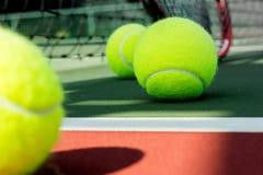 La pallina da tennis con la racchetta alla corte immagine stock libera da diritti