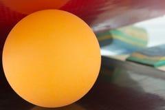 La pallina da tennis gialla è posizionata fra due racchette di ping-pong, fondo del primo piano Immagini Stock Libere da Diritti