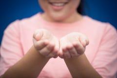 La palma abierta de la mano adolescente de la sonrisa de la muchacha pide el donante Imágenes de archivo libres de regalías