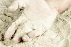 La palma de una mano cubierta con la arena Foto de archivo