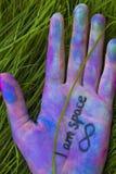 La palma della ragazza è dipinta con i pastelli colorati Il simbolo è l'infinito Concettuale Immagine Stock