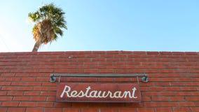 La palma torreggia un ristorante mentre un segno oscilla stock footage