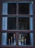La palmatoria en ventana con la ciudad se enciende en fondo Imágenes de archivo libres de regalías