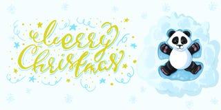 La panda de la inscripción de la caligrafía de la Feliz Navidad está mintiendo en la nieve que juega ángeles de la nieve Foto de archivo libre de regalías