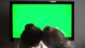 La pantalla verde de observación rubia de pelo largo joven de dos TV y endereza la cabeza metrajes