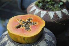 La papaya cortó por la mitad con las semillas en una maceta Fotografía de archivo