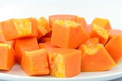 La papaya se corta en pequeños pedazos cerca para arriba Imagen de archivo