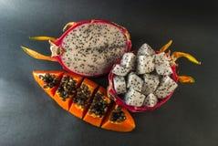 La papaye et le fruit du dragon ont servi à un dessert sur le fond noir Images libres de droits