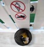 La papelera de reciclaje con basura en un paquete plástico de color negro, una fila dibujó muestras de la prohibición en un fondo imagen de archivo