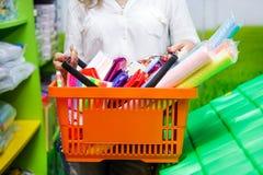 La papeterie verte blanche orange de supermarché d'achats de troley de jeune femme de mail d'achat de panier achète la main image libre de droits