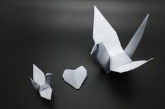 La papiroflexia blanca crane y corazón en medio, papel del pájaro Fotos de archivo libres de regalías