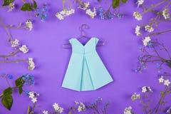 La papiroflexia del papel azul se viste en la suspensión rodeada con las pequeñas flores azules y blancas en el fondo violeta Foto de archivo libre de regalías