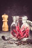 La paprica rovente del peperoncino in barattolo di vetro ed i peperoni seminano il mulino di pepe e della palla sull'ingrediente  immagini stock