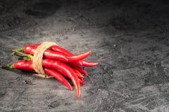 La paprika candente de la pimienta de chiles adentro y las pimientas siembran la bola en la tabla de piedra imagen de archivo libre de regalías