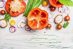 La paprika roja con el top del corte, alista para rellenar y los ingredientes de cocinar sabrosos en el fondo de madera rústico b Imagen de archivo libre de regalías