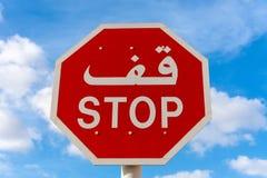 La parada firma en inglés y árabe con el cielo azul y las nubes en fondo fotografía de archivo libre de regalías