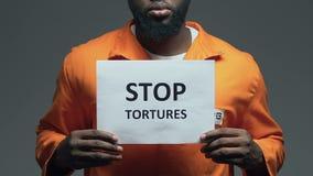 La parada tortura frase en la cartulina en las manos del preso afroamericano, asalto almacen de video